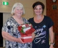 Barbara McGilvray, committee member, receives a floral arrangement from Teena Wallace, assistant musical director, at the Christmas Function, 18th December 2013